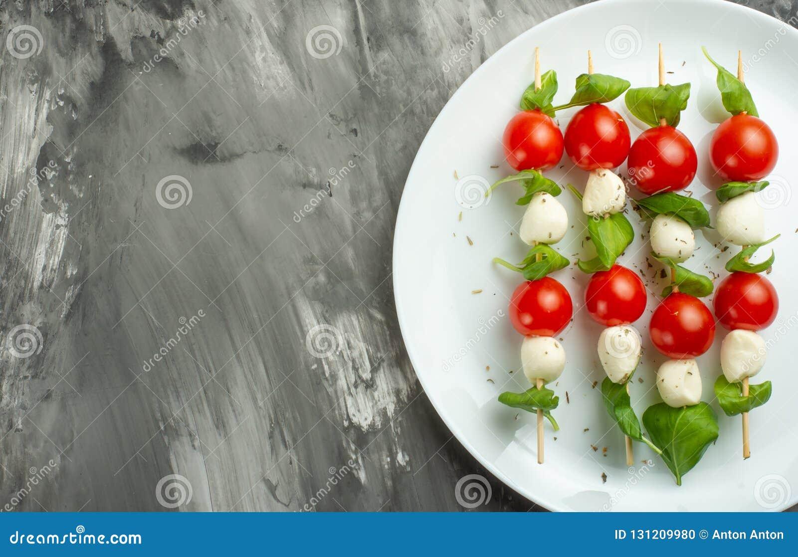 Salade Caprese - kebab met tomaat, mozarella en basilicum, Italiaanse keuken en een gezond vegetarisch dieet op een donkere achte