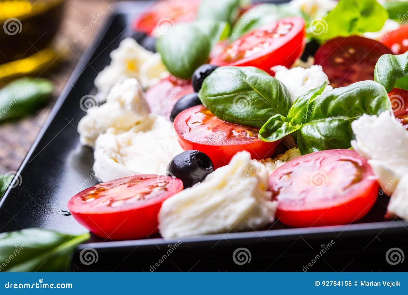 Salade caprese Salade méditerranéenne Basilic de tomates-cerises de mozzarella et huile d olive sur la vieille table de chêne Cui