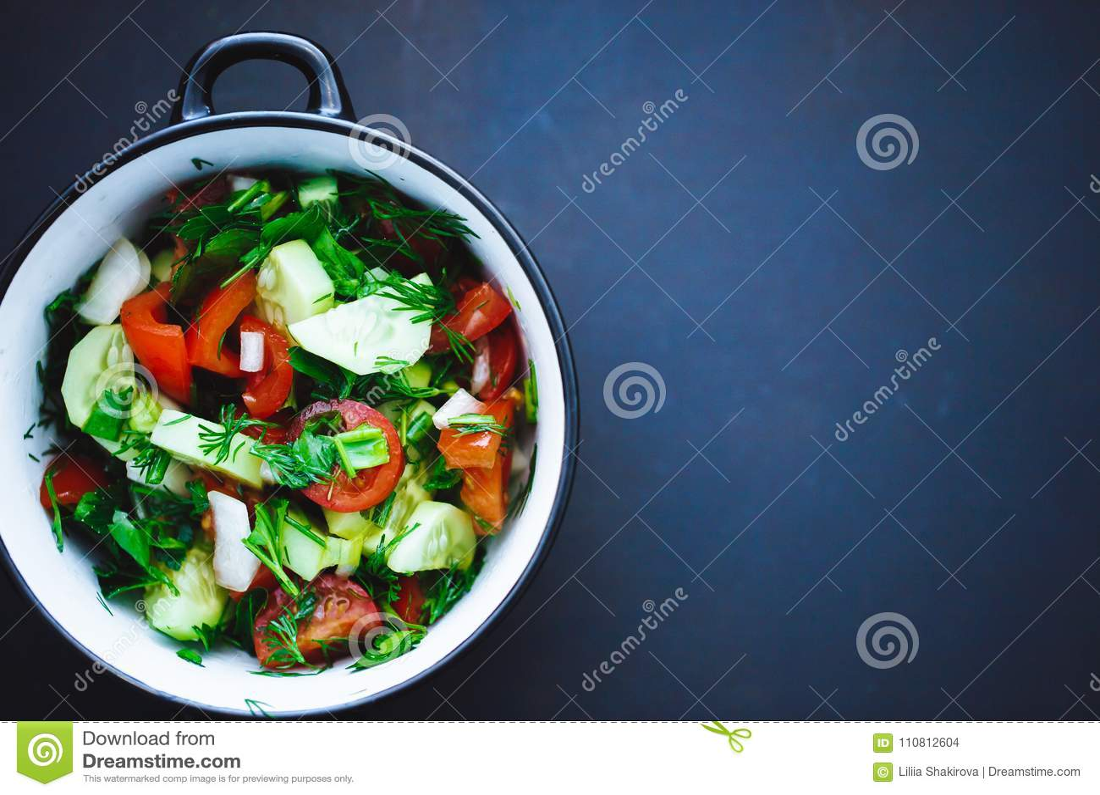 Salade d été des légumes frais dans un plat sur un fond noir, tomates, concombres, aneth, persil, oignon Fermez-vous, vue supérie
