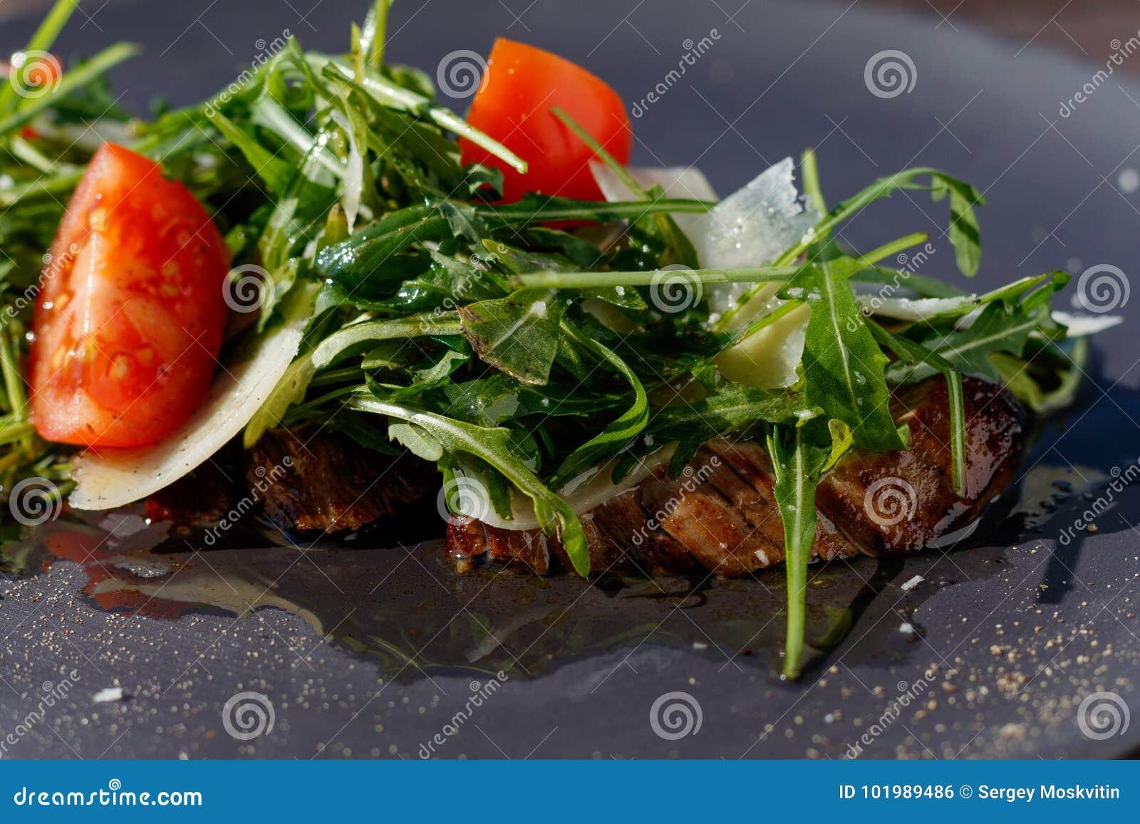 Salade de bifteck de veau avec l arugula, laitue, moitiés de petites tomates-cerises, parmesan