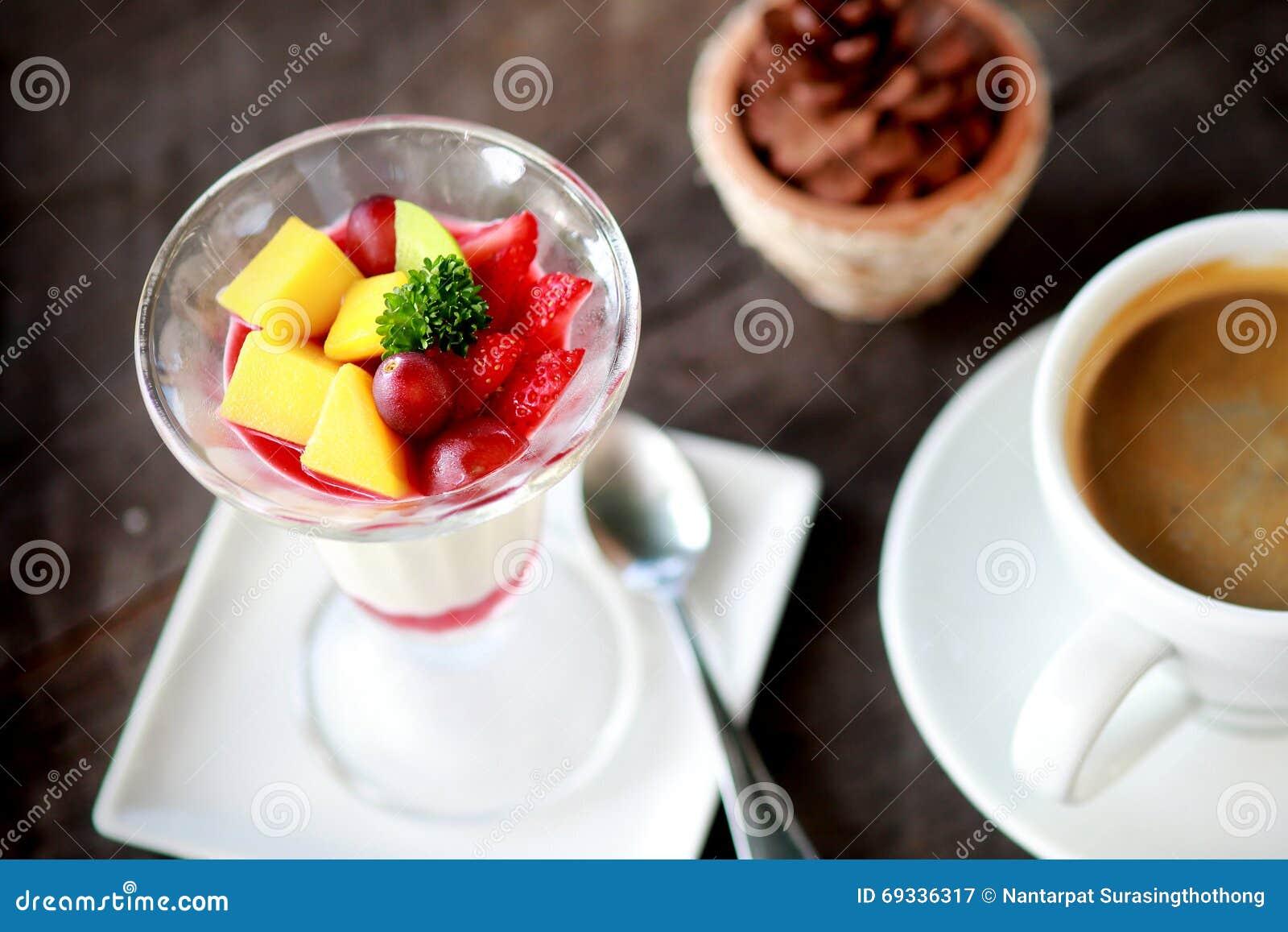 Salade de fruits avec le pudding de gelée en verre et café dans la tasse blanche