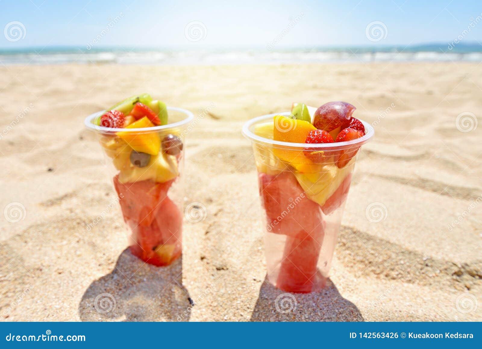 Salade de fruits dans des tasses en plastique sur la plage d été