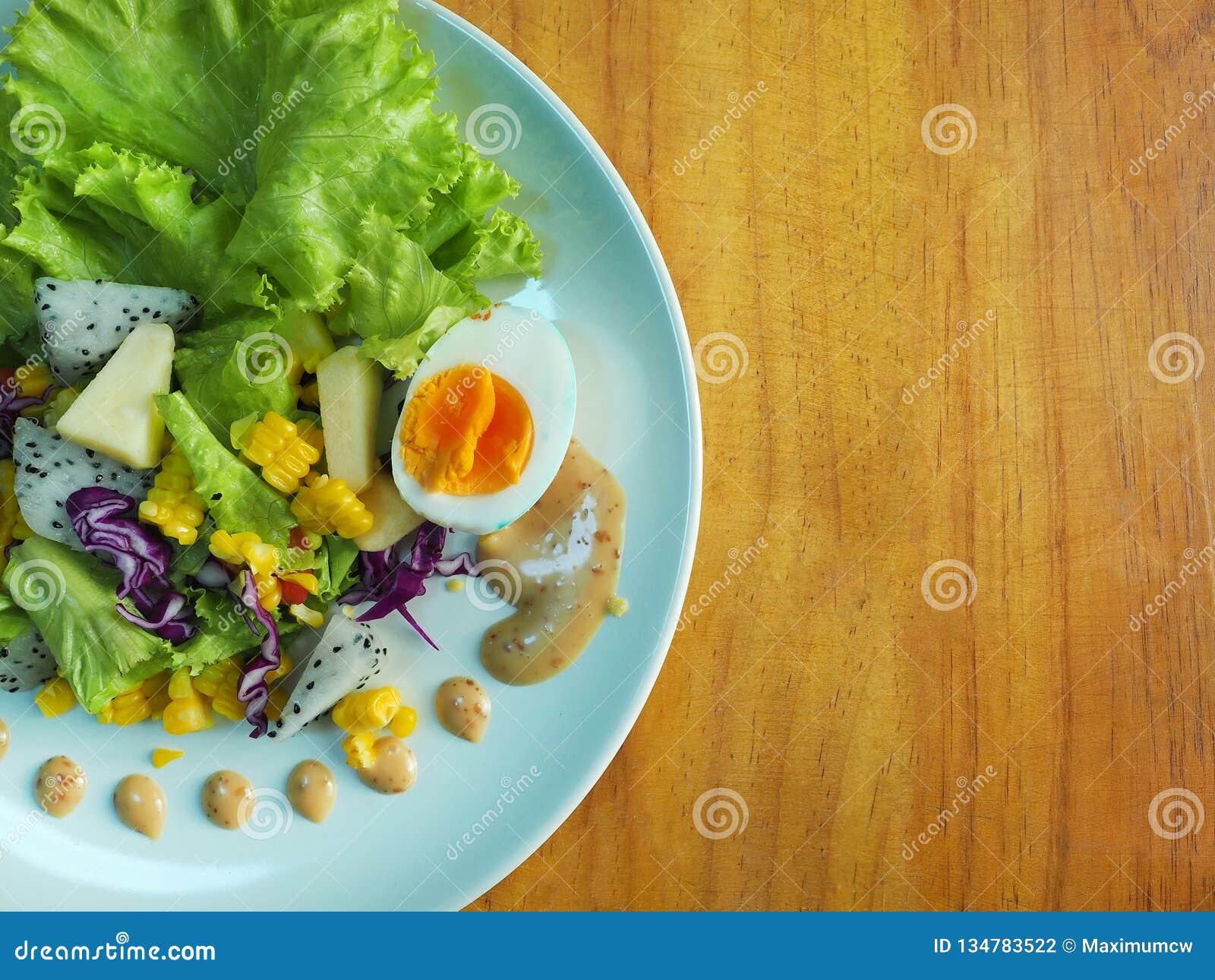 Salade de fruits et sauce salade avec le fond en bois