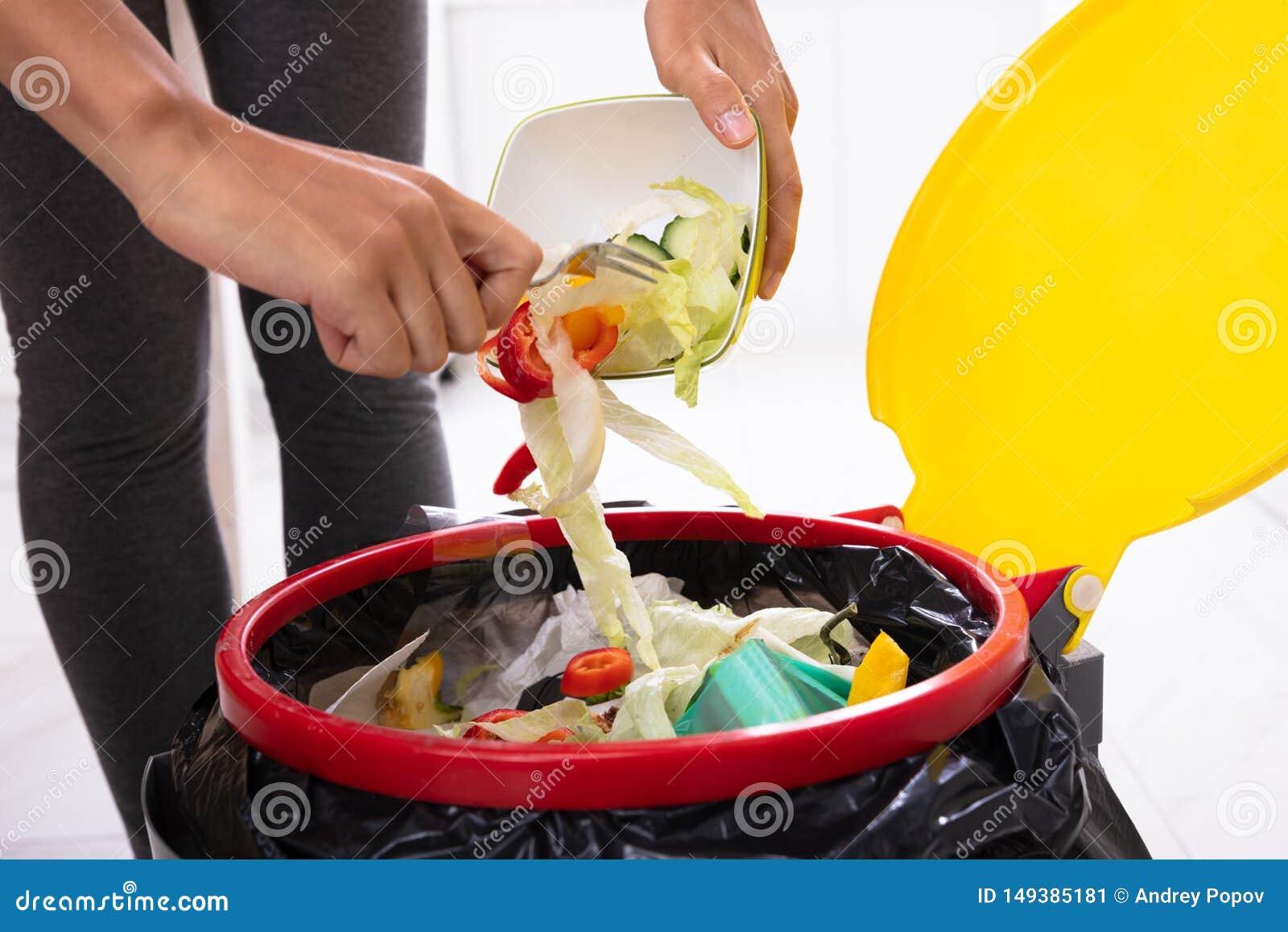Salade de lancement de femme dans la poubelle