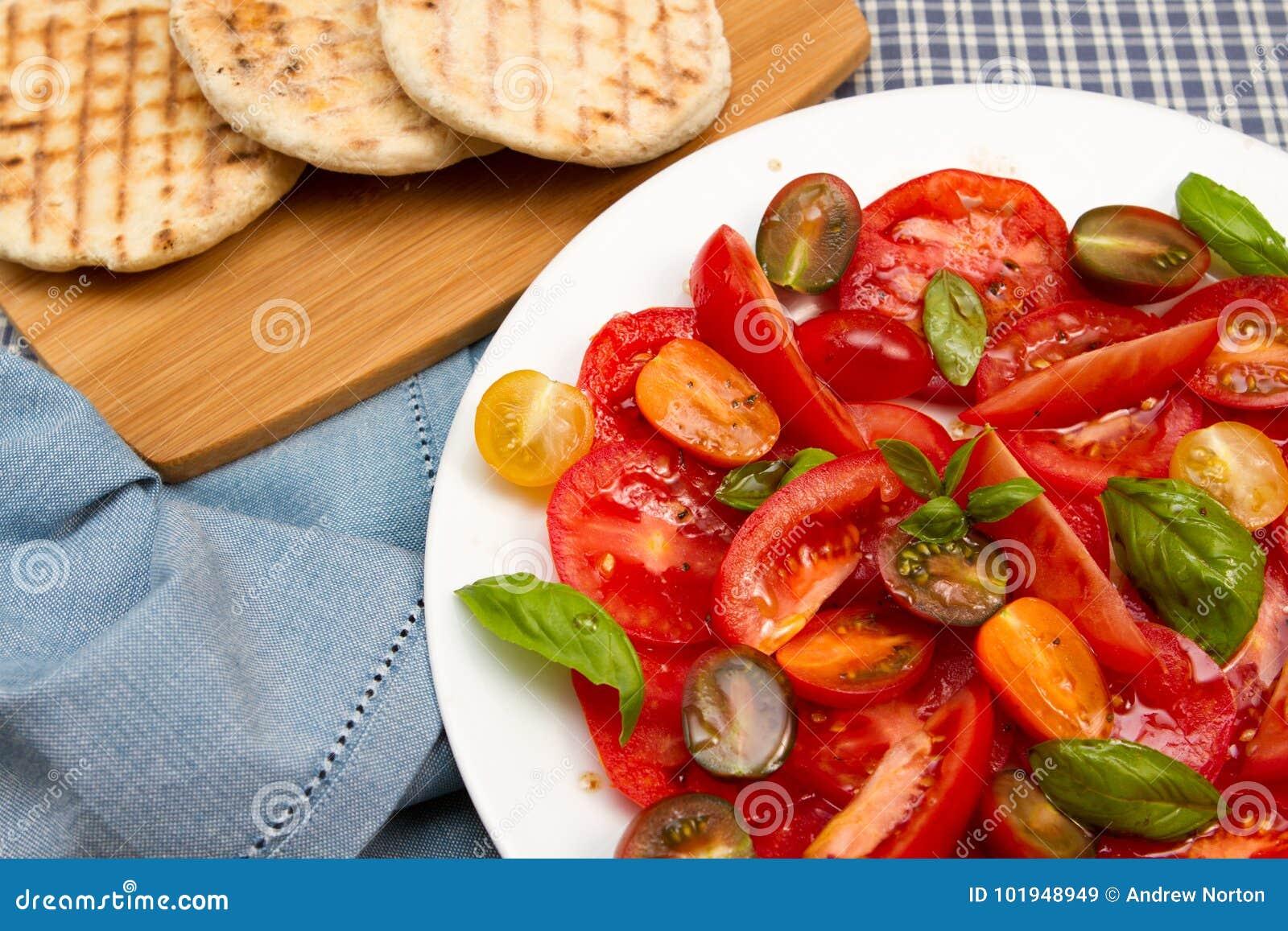 Salade de tomatoe d héritage avec des pains plats