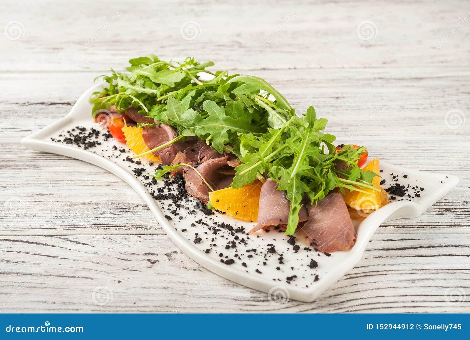 Salade de viande avec les oranges et l arugula dans un plan rapproché blanc de plat Casse-croûte de jamon et arugula avec des ora