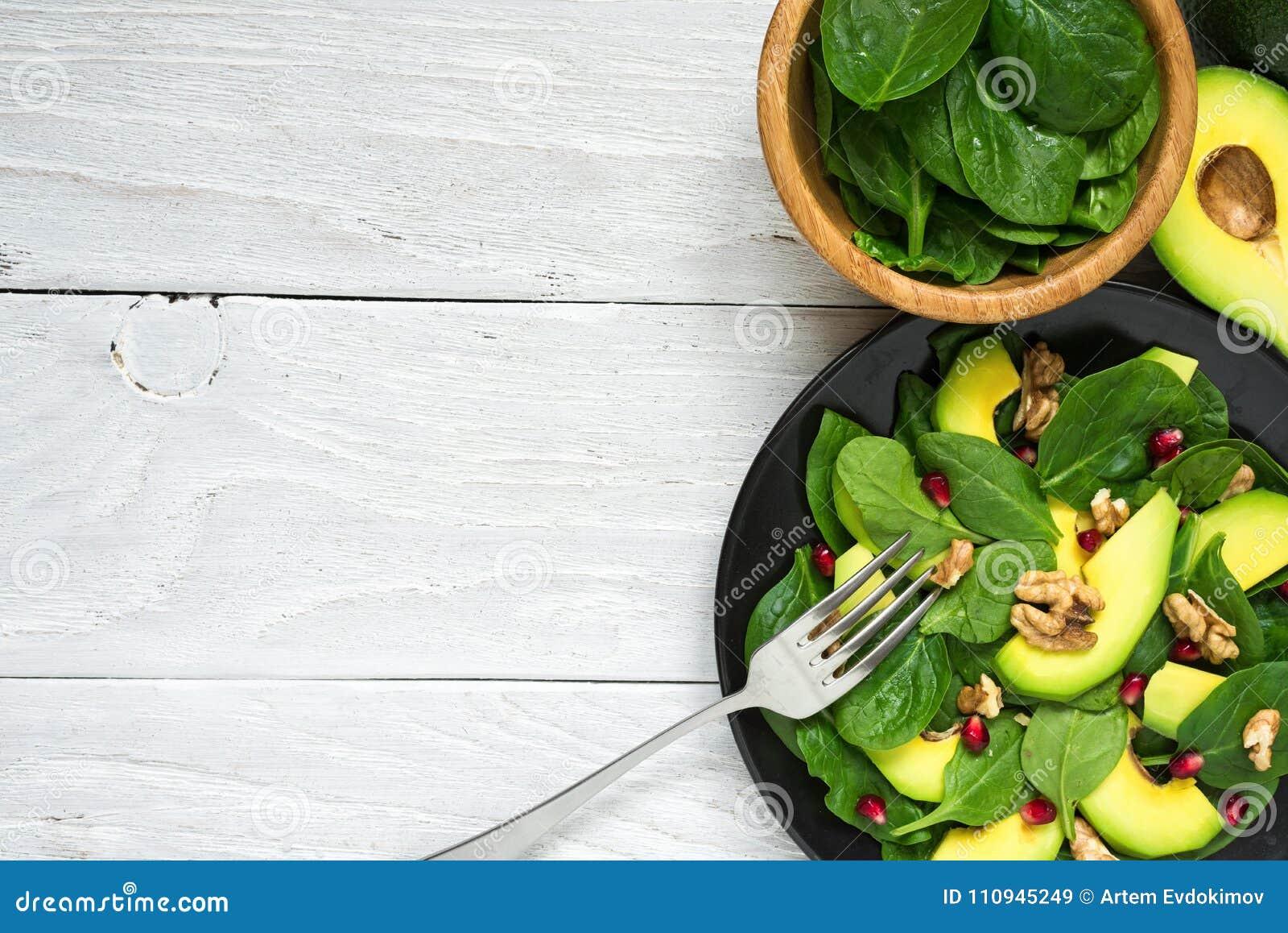 Salade fraîche avec l avocat, les épinards, la grenade et les noix dans le plat noir avec la fourchette Nourriture saine