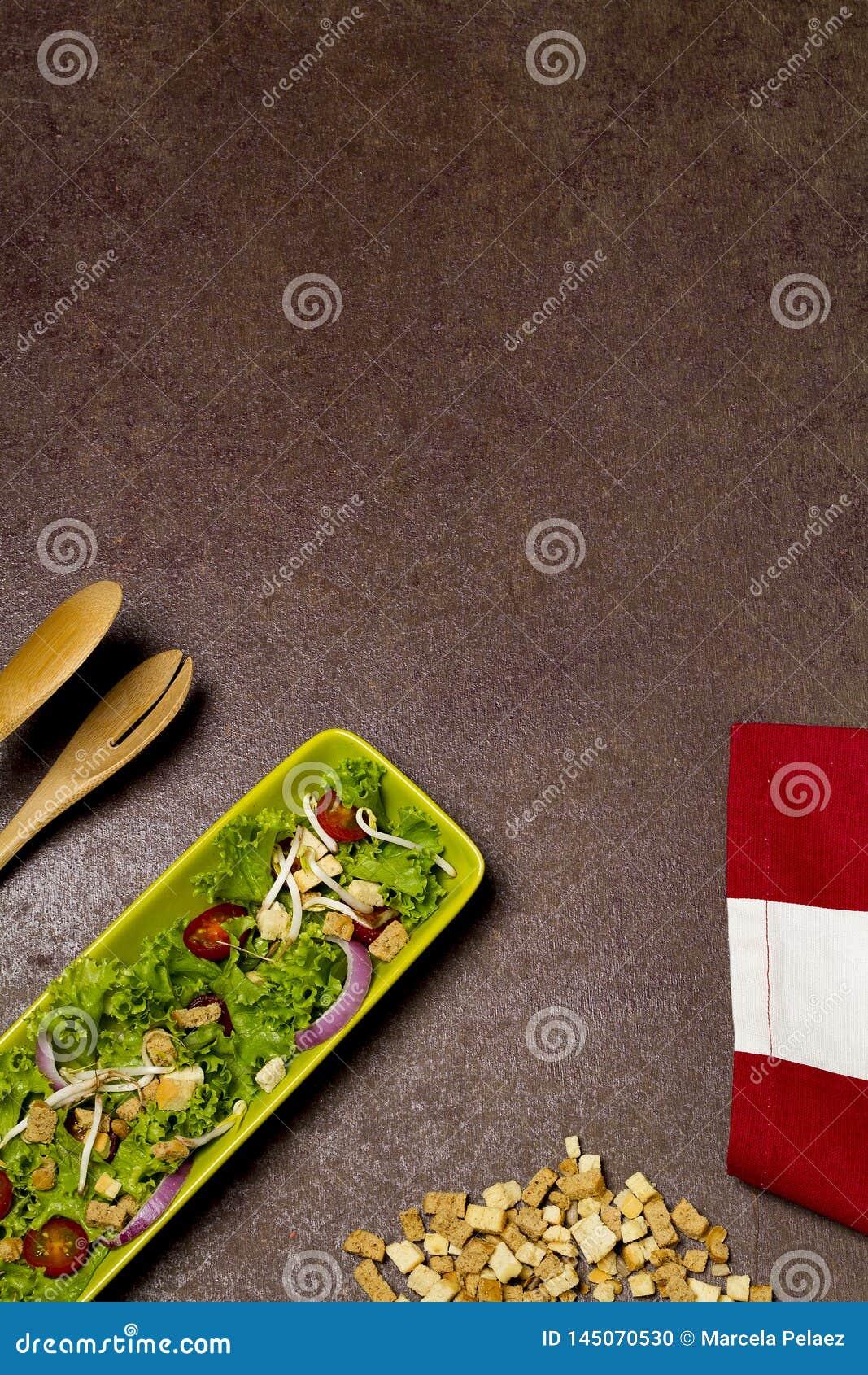 Salade fraîche de laitue et d oignon de tomate avec le tissu rayé rouge, les dentelles de pain et la cuillère en bois