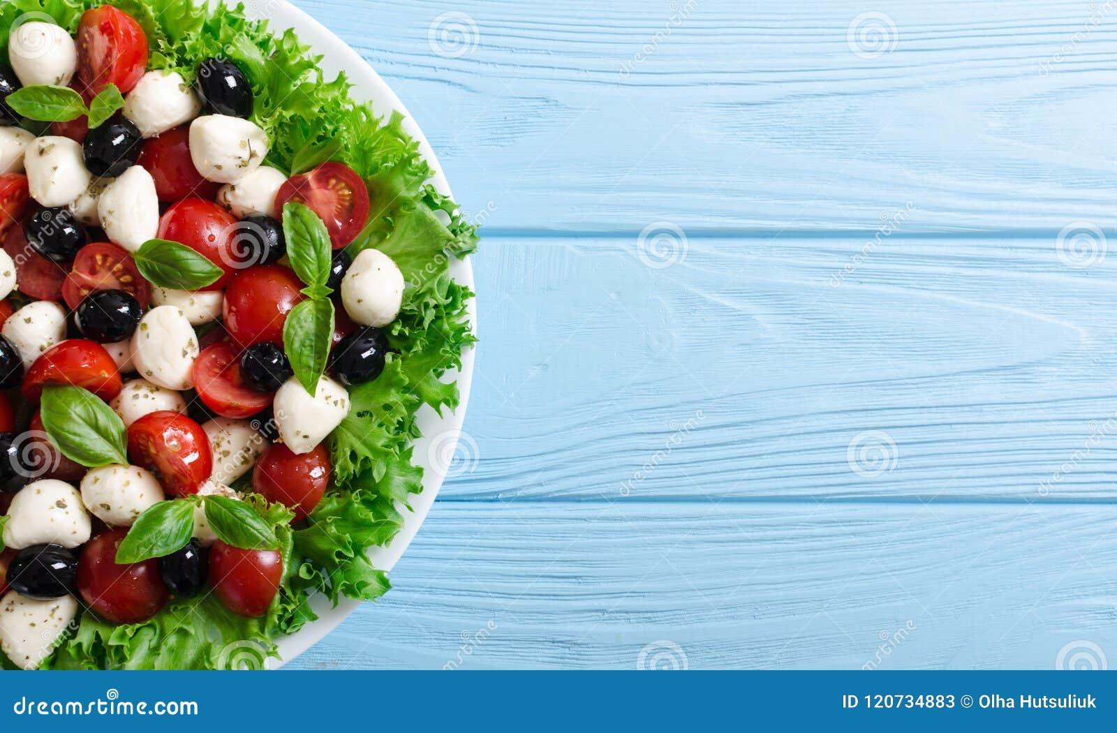 Salade met basilicum, tomaten, olijven en mozarella