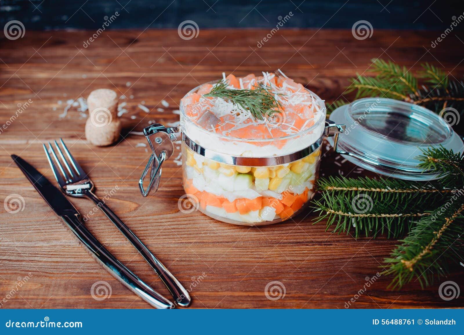 Salade saumonée sophistiquée avec le parmesan et fourchette sur un fond en bois