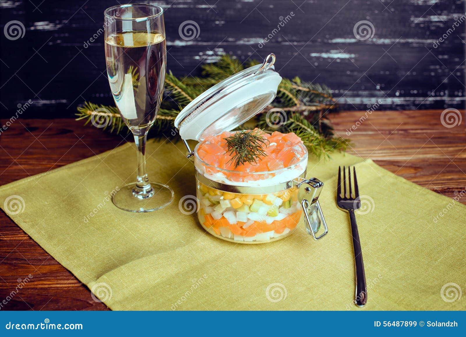 Salade sophistiquée avec le champagne et fourchette sur un fond en bois