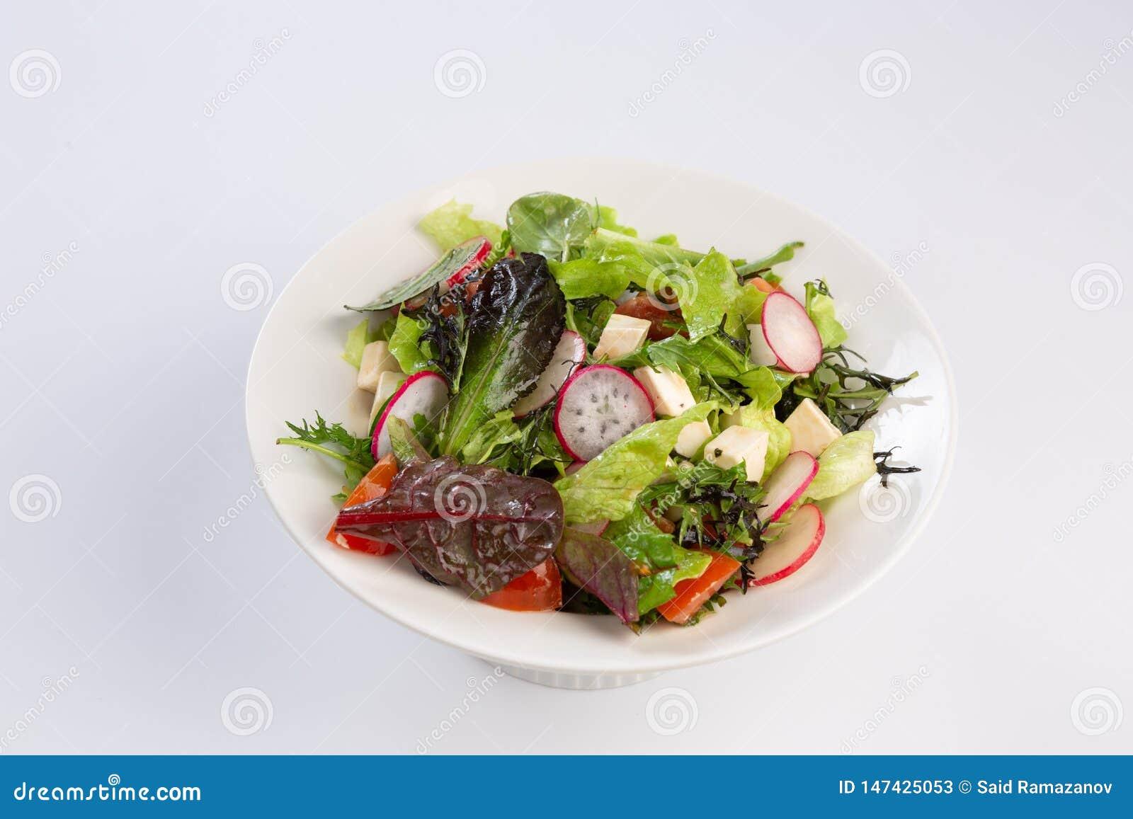 Salade van greens, kaas en radijs op witte achtergrond