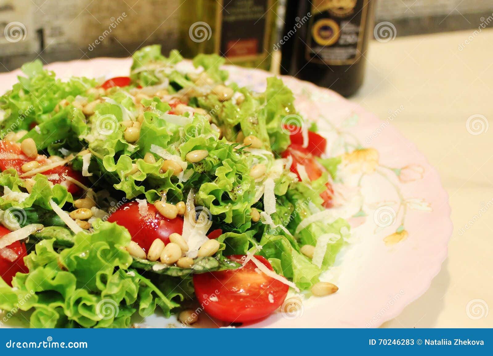 salade verte avec les tomates, le parmesan et les pignons image