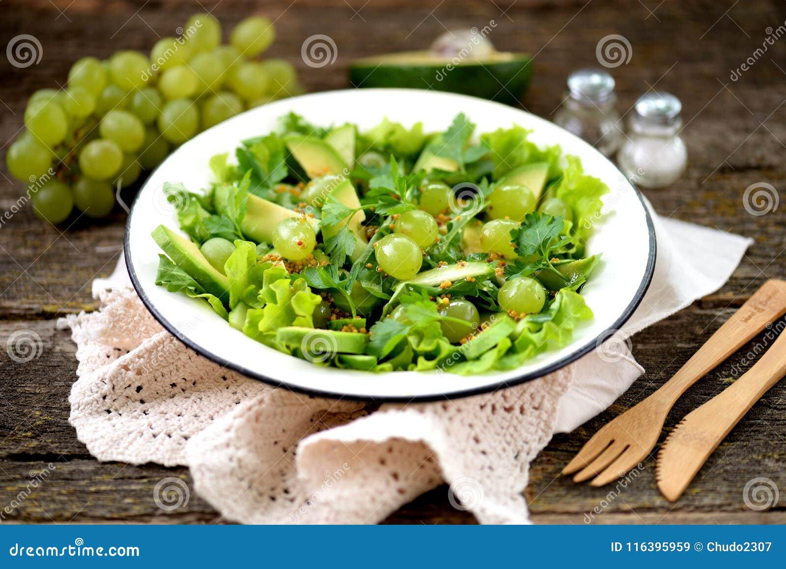 Salade verte saine d avocat, de concombre, de raisins, de persil et de laitue avec le habillage, le vinaigre balsamique et le gra