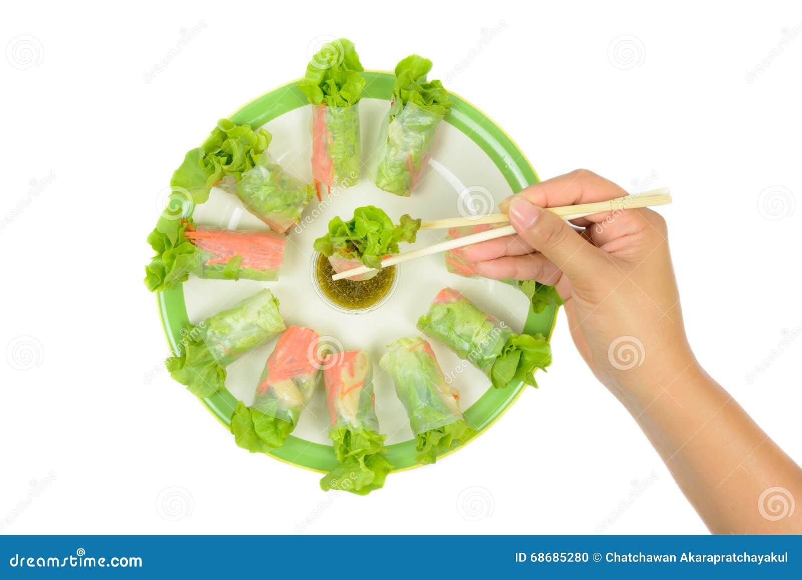 Saladebroodjes met de eetstokjes die van de handgreep in zeevruchtensaus onderdompelen