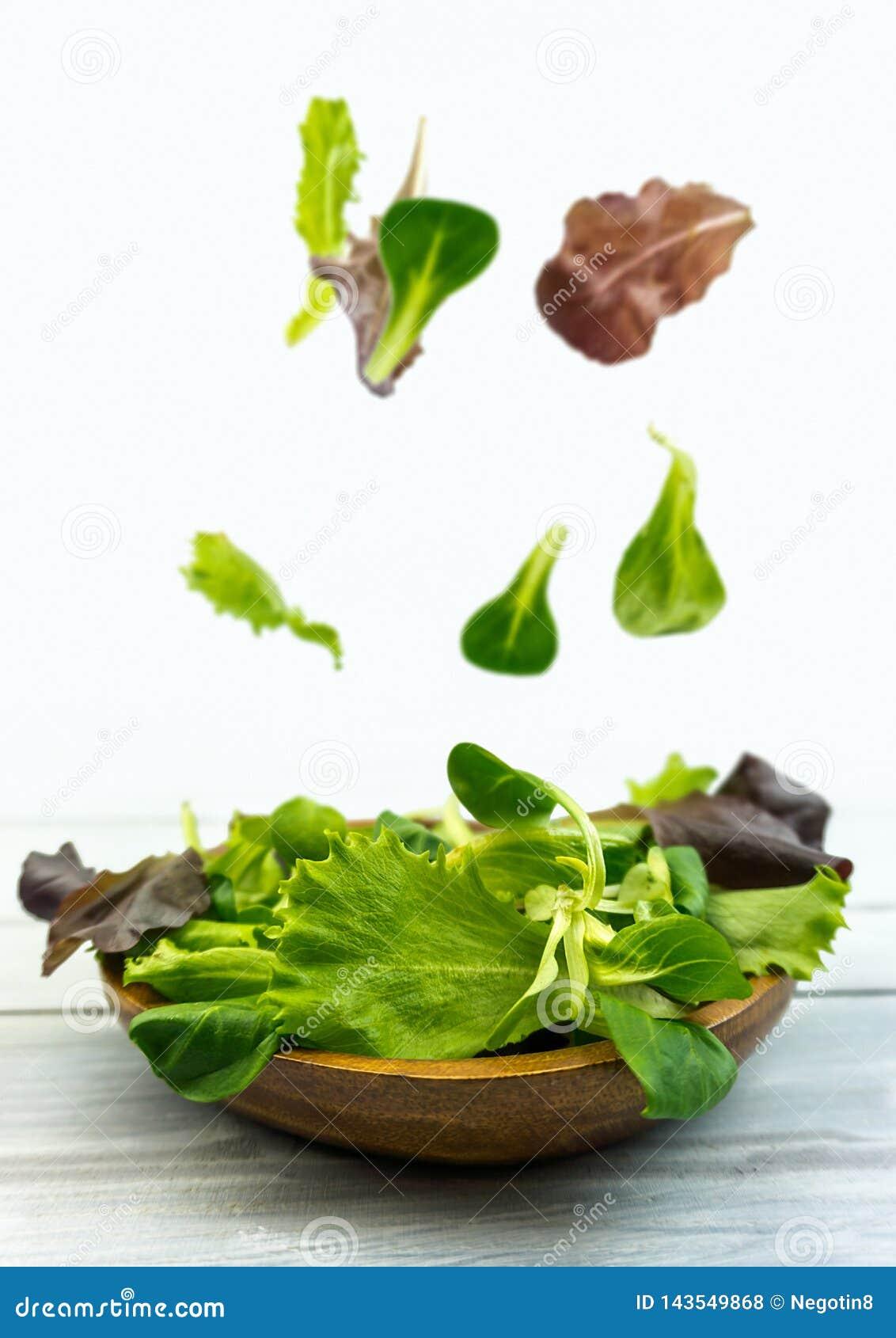 Saladeexplosie met arugula, bieten, spinazie en spruiten op heldere houten raad