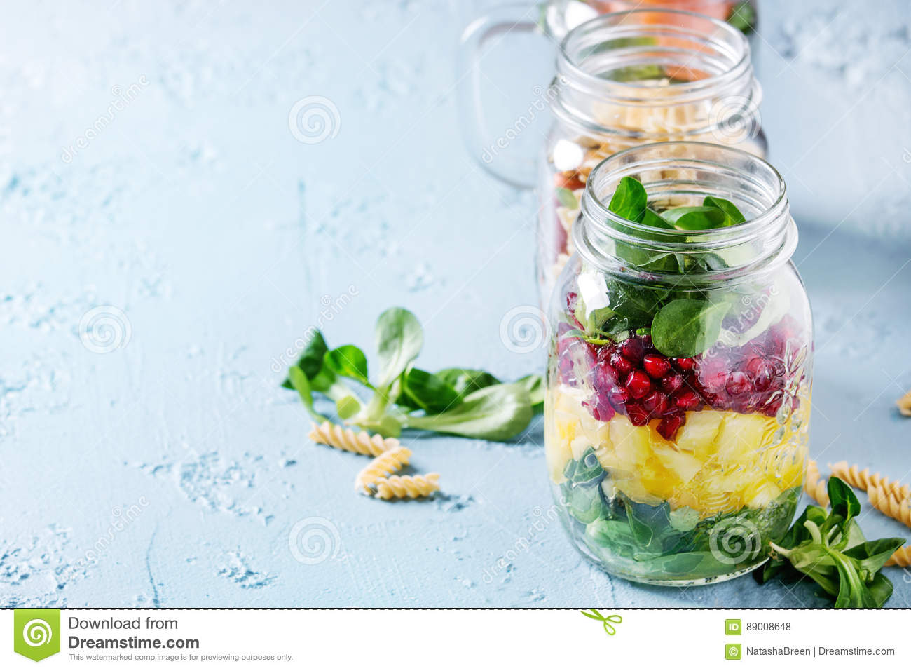 Fruit Salad Mango Pomegranate Greens Vegetables Wholegrain Pasta Carrots And Cauliflower Salmon Standing Over Blue Texture Background Food To Go