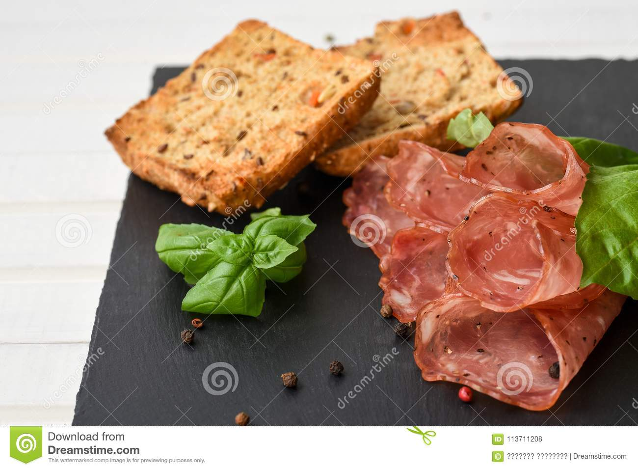 Salami smoked sausage slices basil leaves, peppercorns and bread