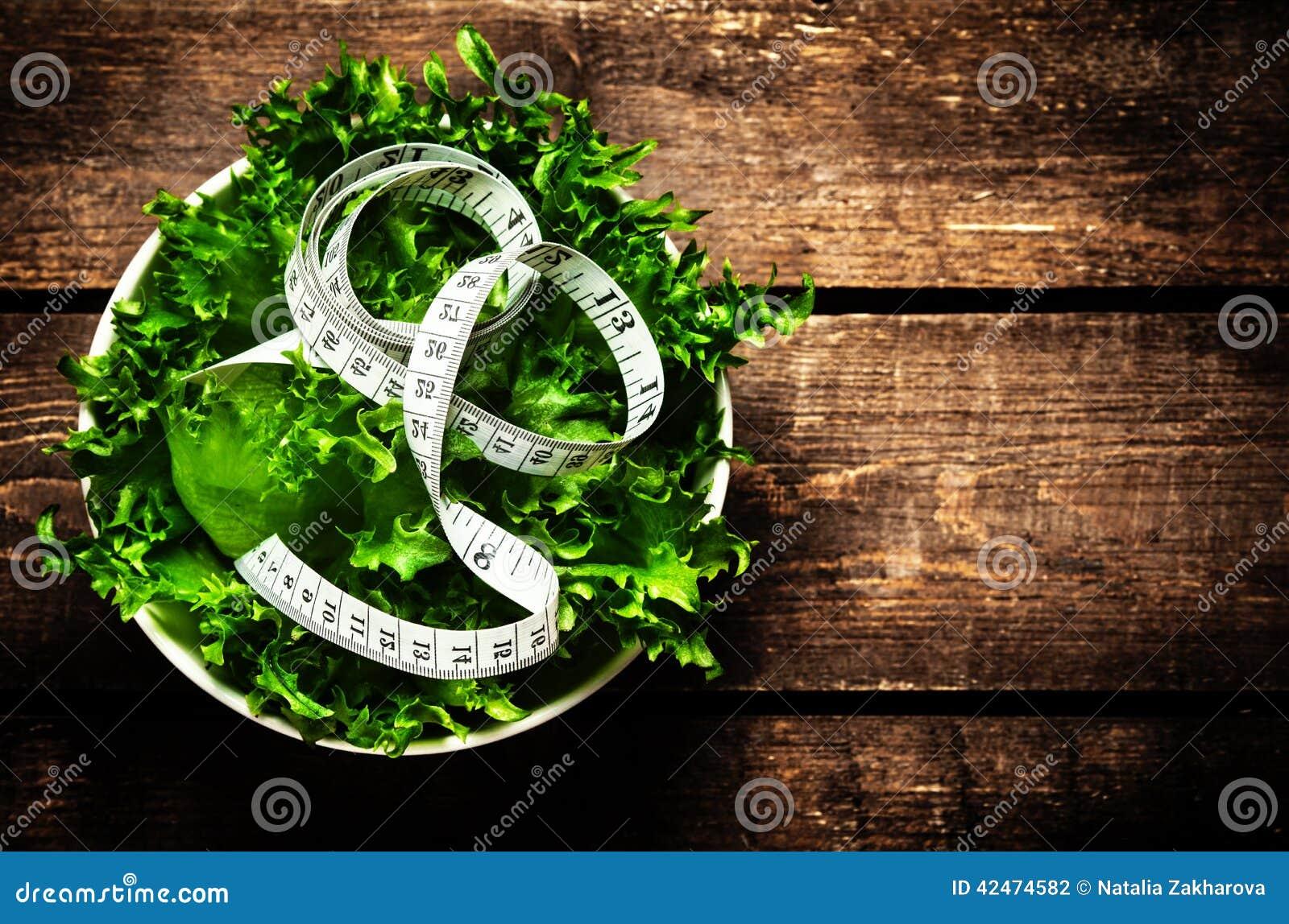 Salat und messendes Band auf rustikalem hölzernem Hintergrund Nähren Sie Nahrung