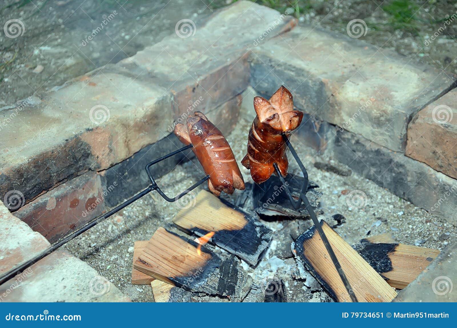 Salchicha de asado a la parilla dos sobre un fuego en chimenea del ladrillo