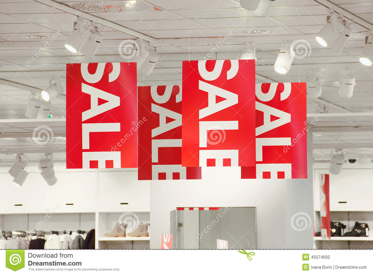 A photo of a sale sign with a clothing store in the background