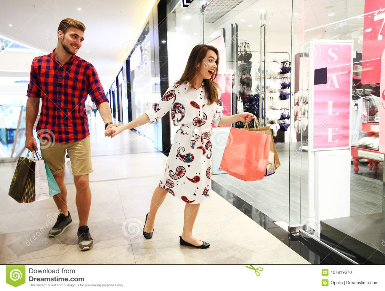 053f12727f Sale, consumerism and people concept - happy young couple with shopping  bags walking in mall