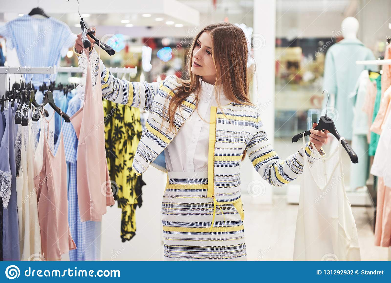 Sale, fashion, consumerism and people concept - happy young woman with shopping bags choosing clothes in mall or