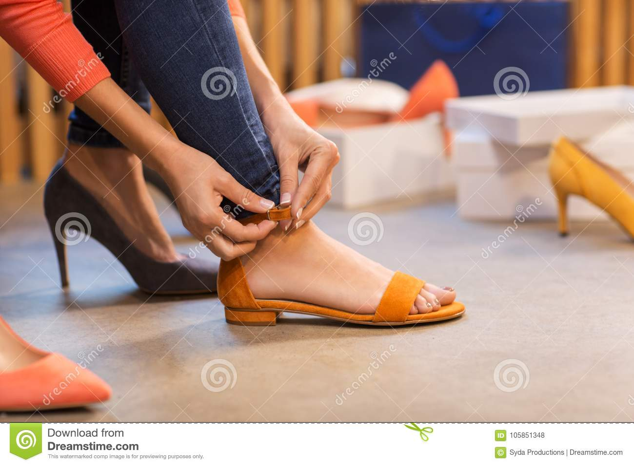 Young woman trying sandals at shoe store