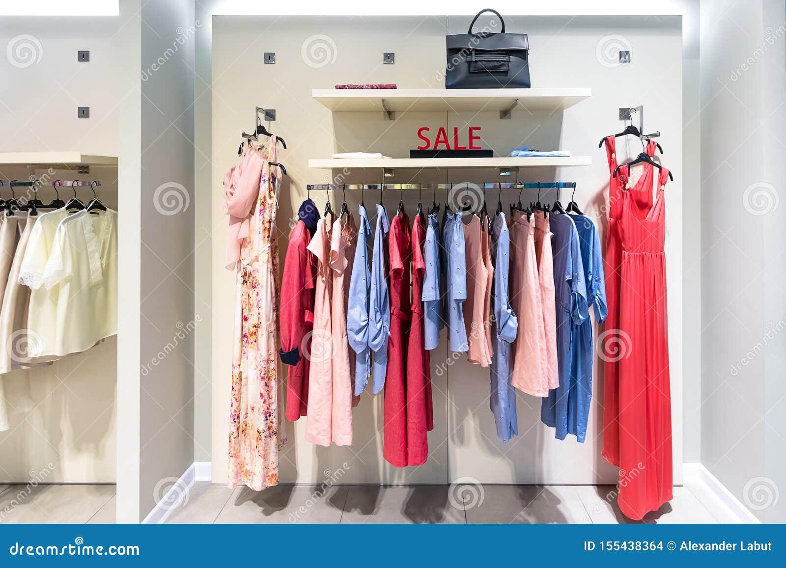 Sale undertecknar in kvinnornas bekläda lager Färgrika klänningar på hängare i en detaljhandel shoppar Säsongförsäljning, mode oc