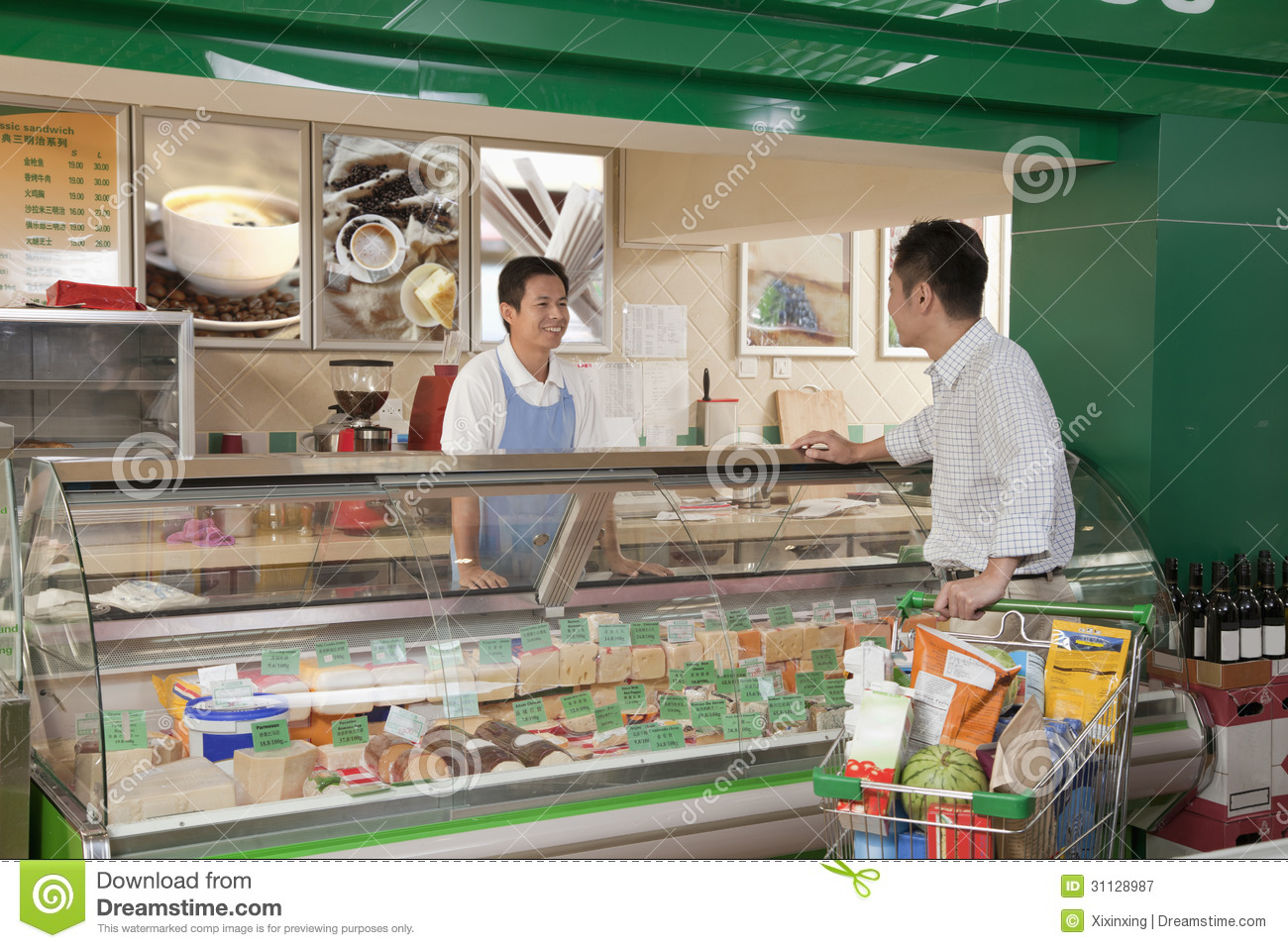 s clerk smiling and assisting man at the deli counter in s clerk smiling and assisting man at the deli counter in supermarket