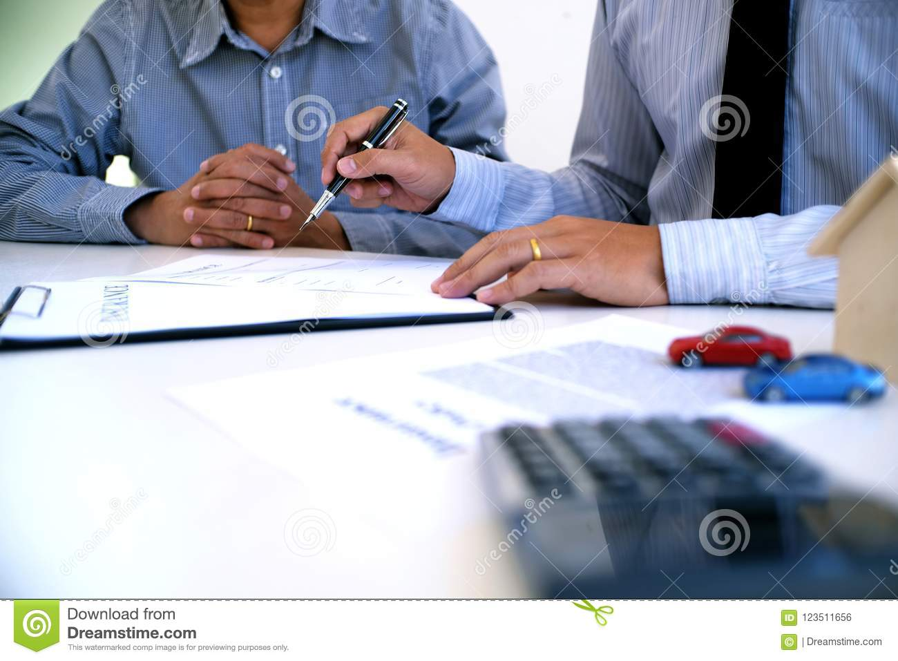 Sales manager giving advice application form document, considering mortgage loan offer for car and house insurance.