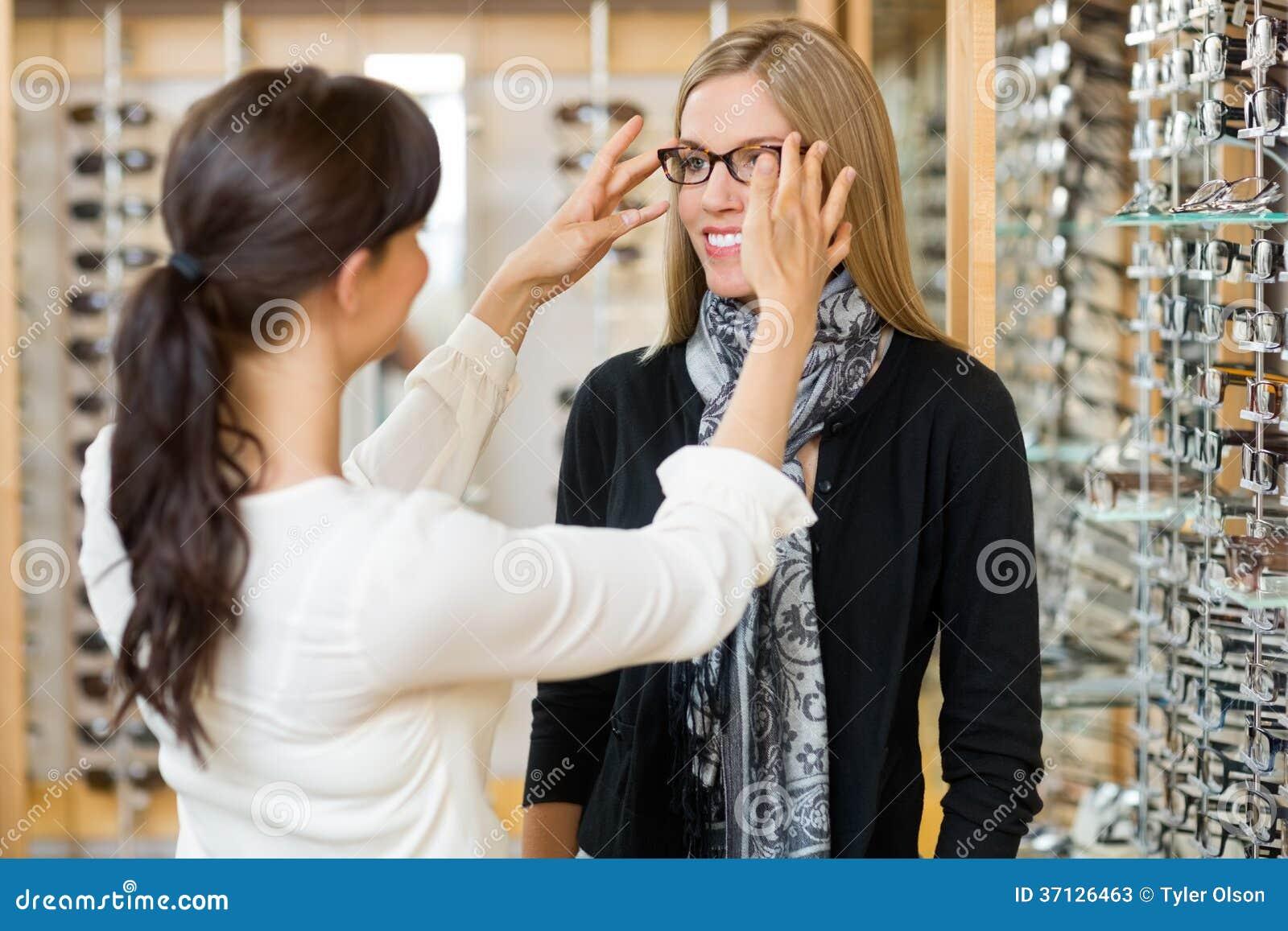 Salesgirl помогая клиенту к в нося стеклам