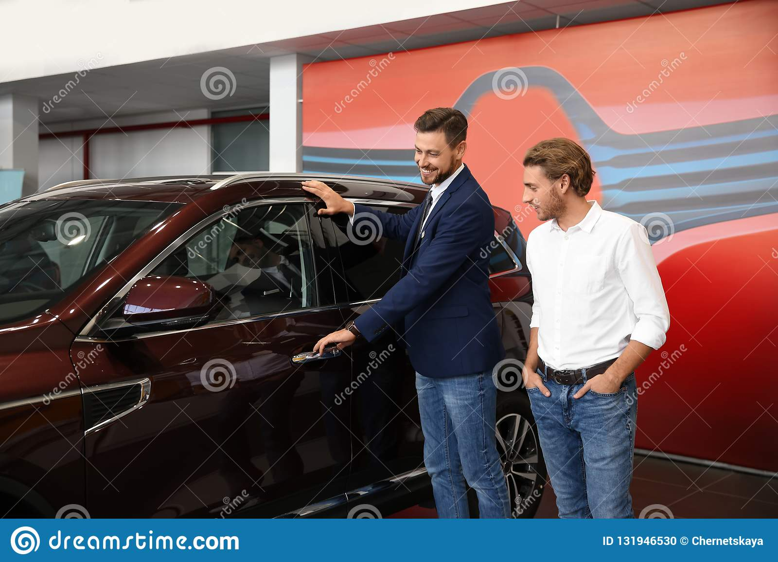 Salesman with customer in modern car