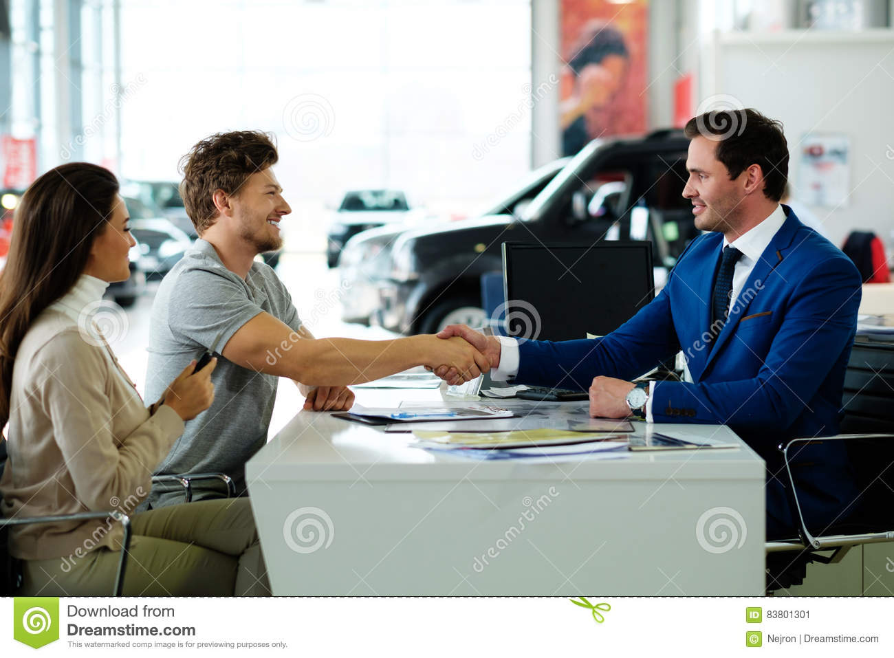 Salesman and customer shaking hands congratulating each other at the dealership showroom