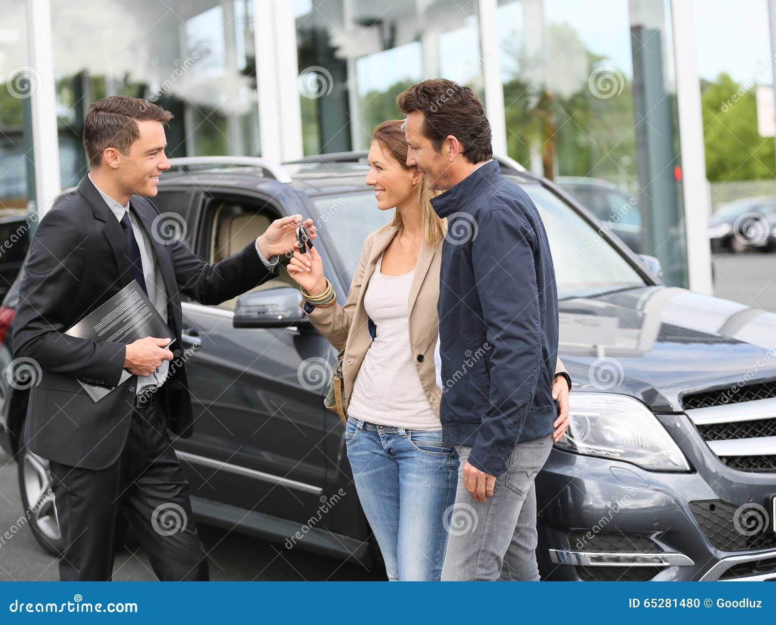 Salesman handing keys of new car to happy clients