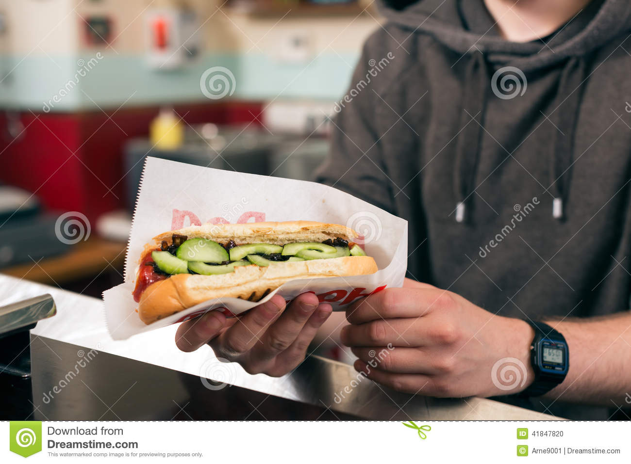 Salesman with hotdog in fast food snack bar