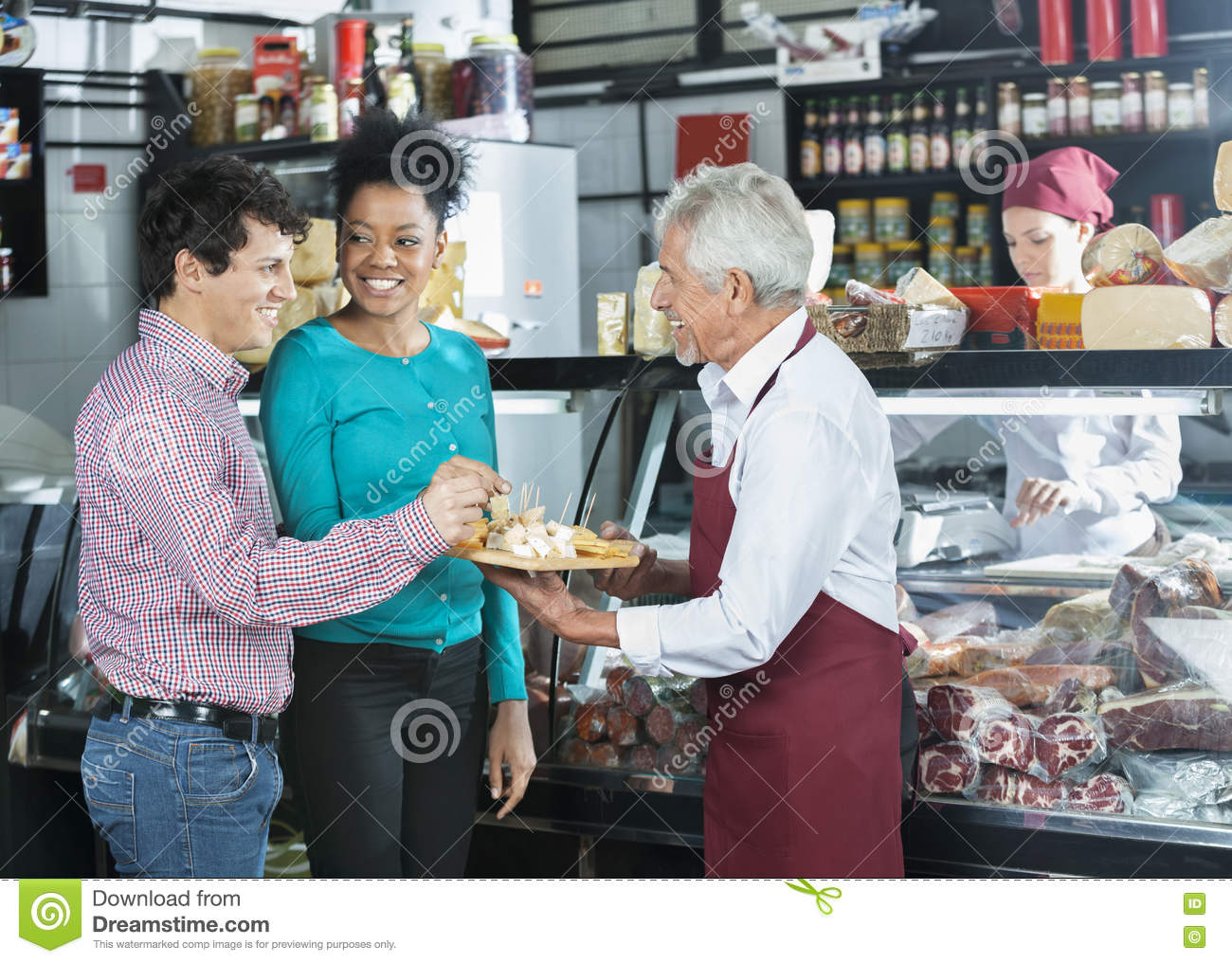 Salesman Offering Samples To Customers In Cheese Shop