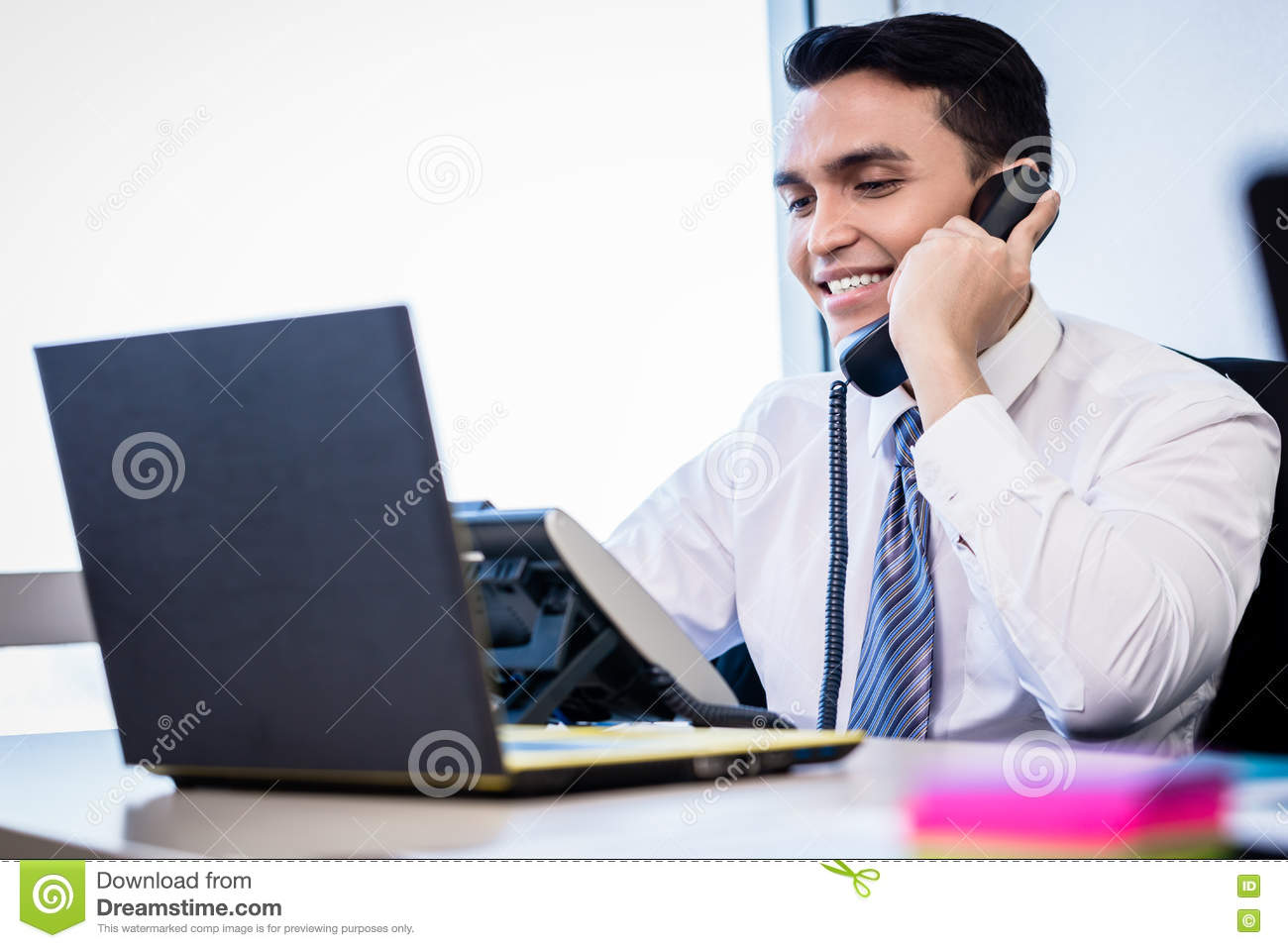 Salesman in office making phone call