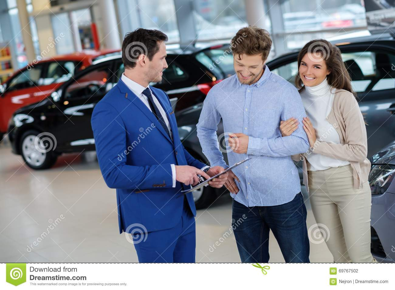 Salesman talking to a young couple at the dealership showroom.