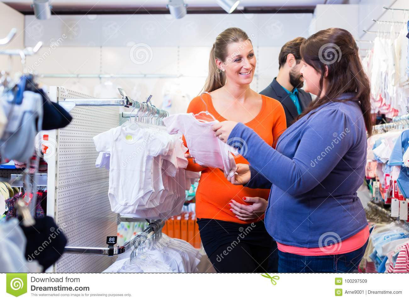 salesperson with couple buying baby clothes in shop stock image