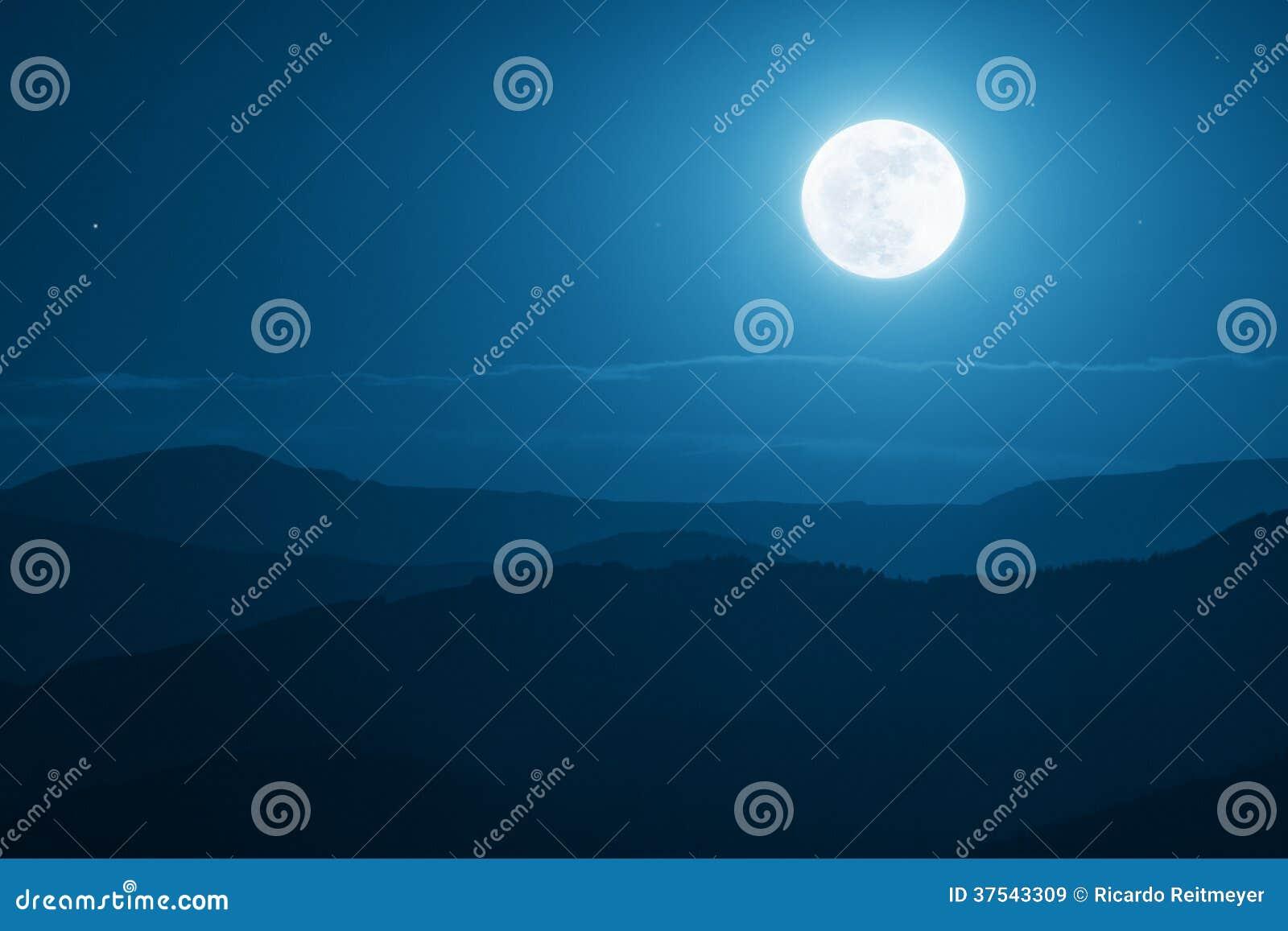 Salida de la luna dramática de la montaña con el cielo azul y las sombras profundos