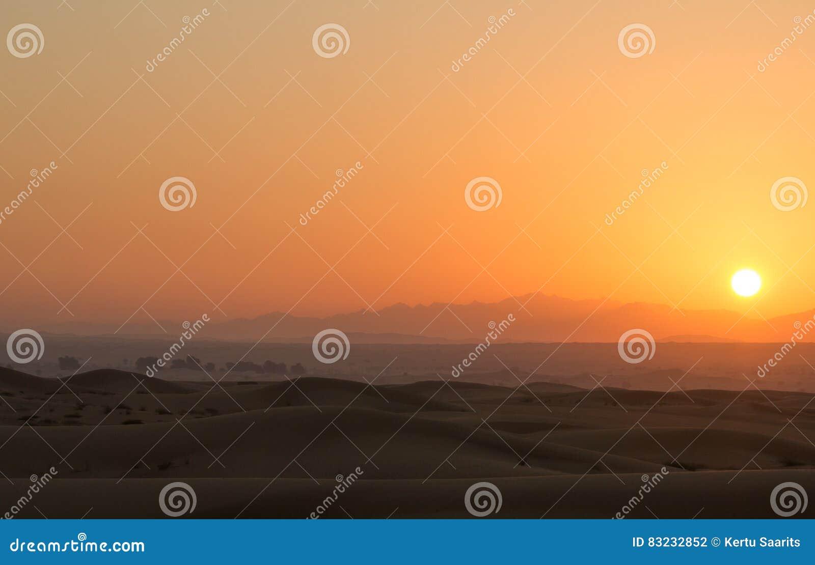 Salida del sol caliente en las dunas del desierto de Dubai, United Arab Emirates