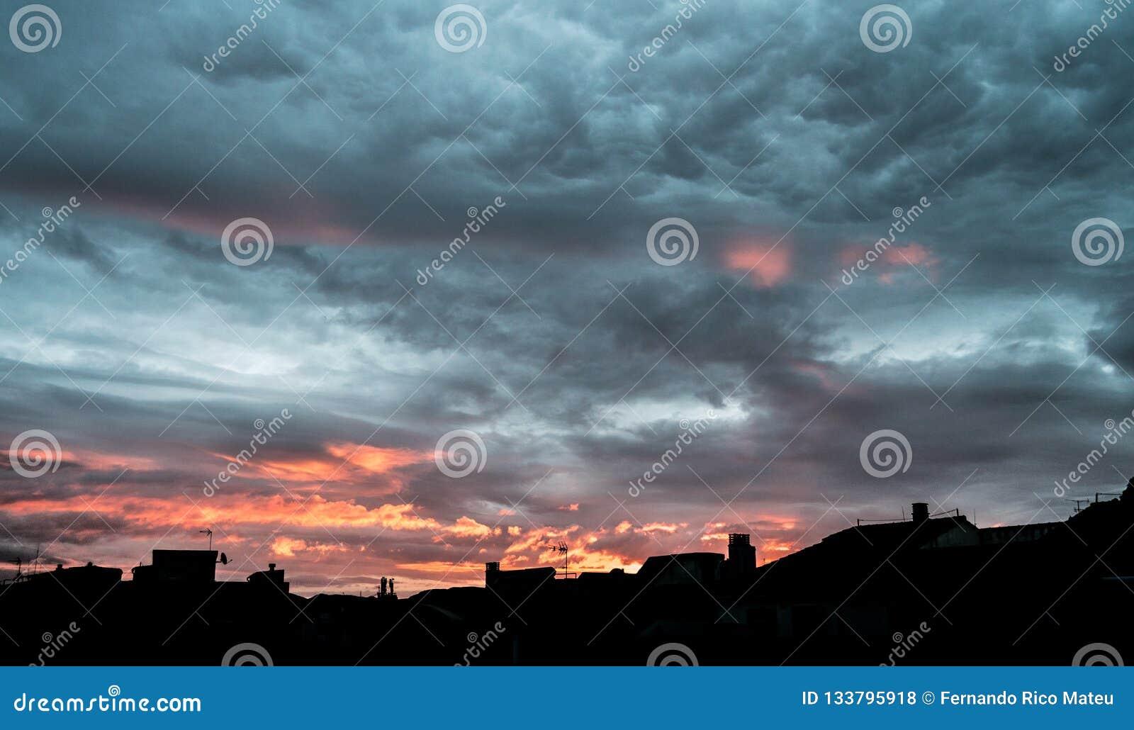 Salida del sol del cielo nublado que sorprende Nubes dramáticas asustadizas de la tormenta anaranjado oscuro en salida del sol he