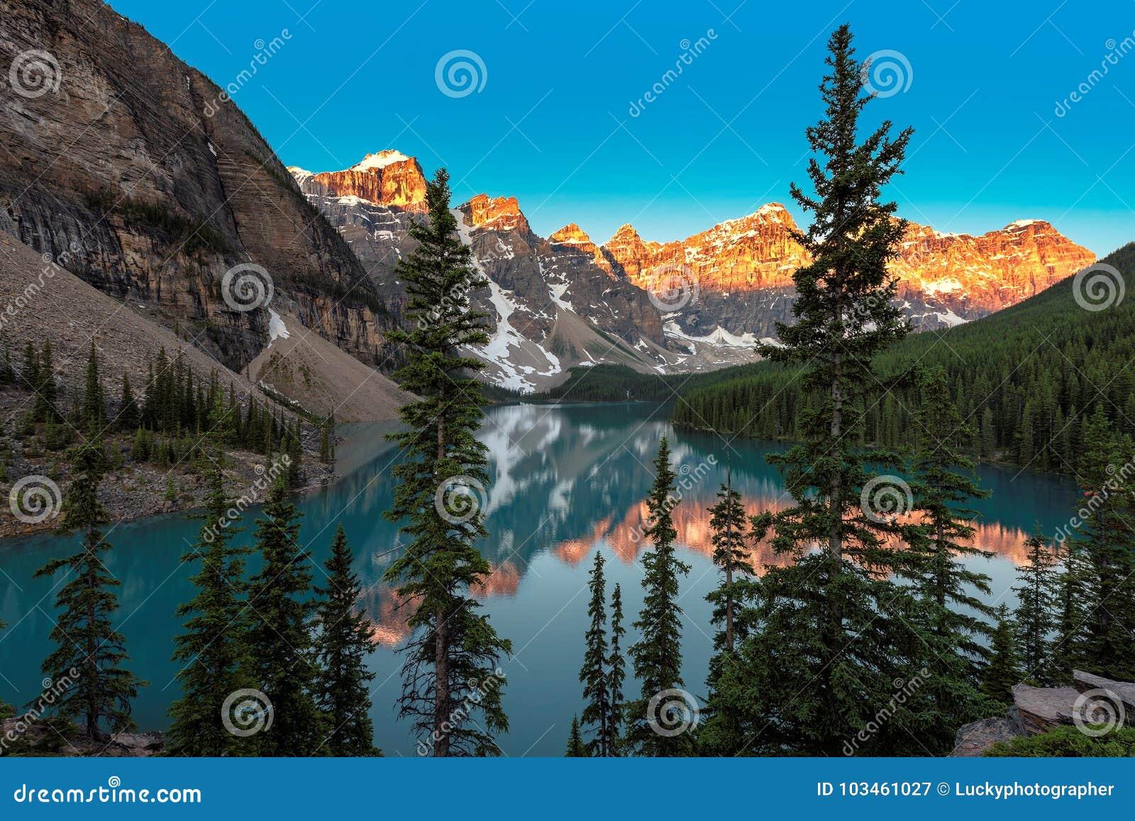 Salida del sol en el lago en montañas rocosas canadienses, parque nacional de Banff, Canadá moraine