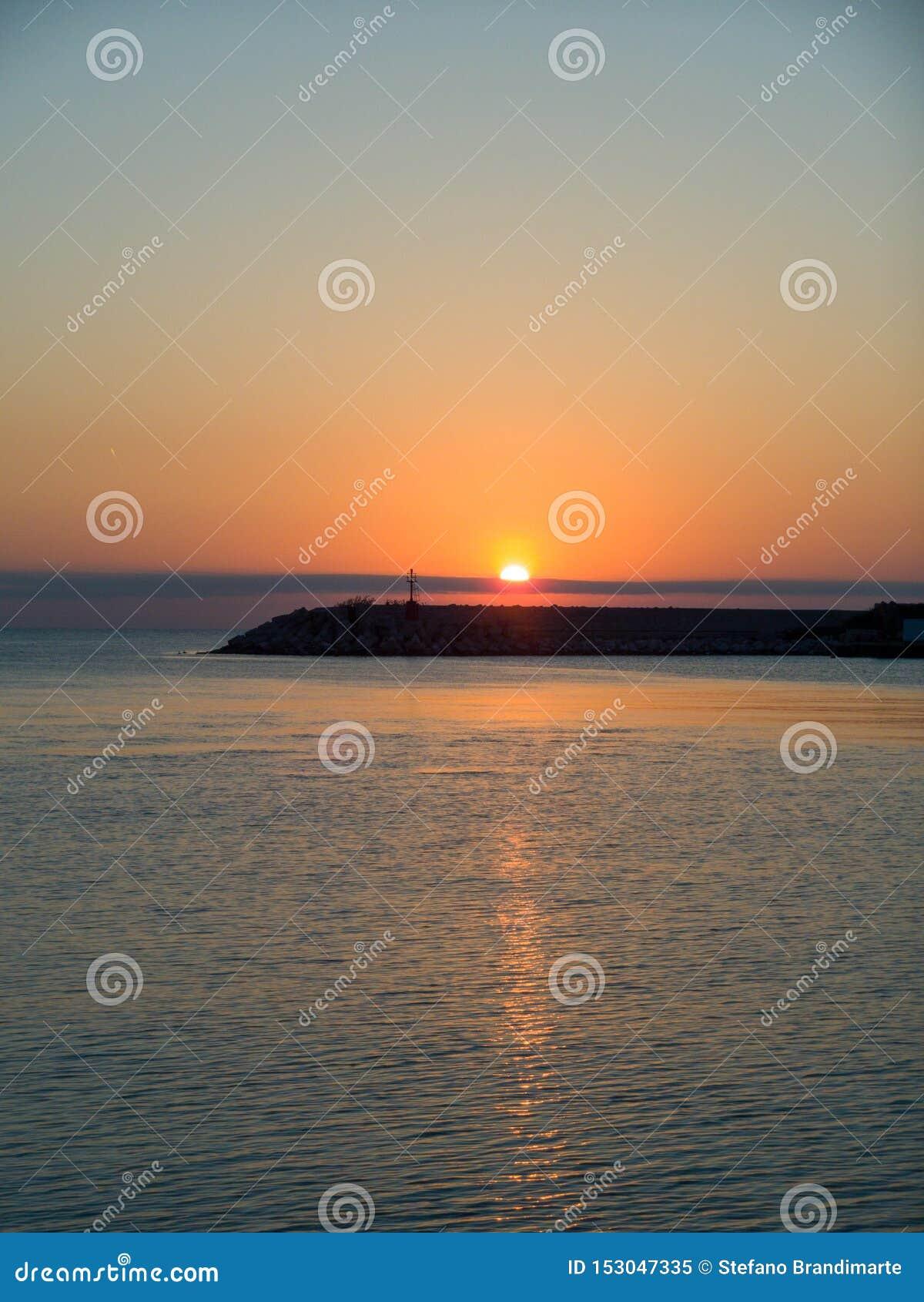 Salida del sol en el mar adriático, reflexiones de la luz del sol en el agua