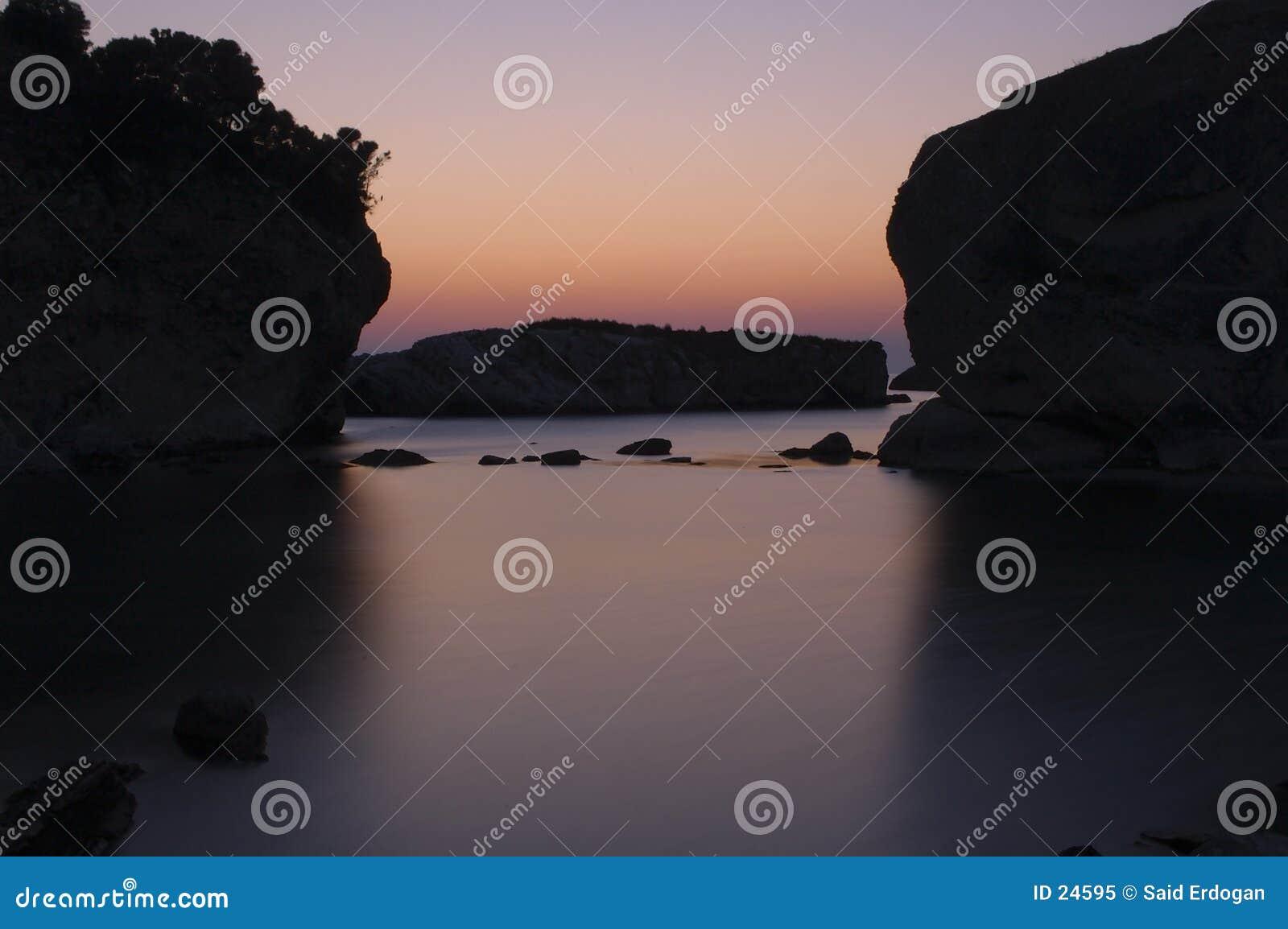 Salida del sol en el mar rocoso