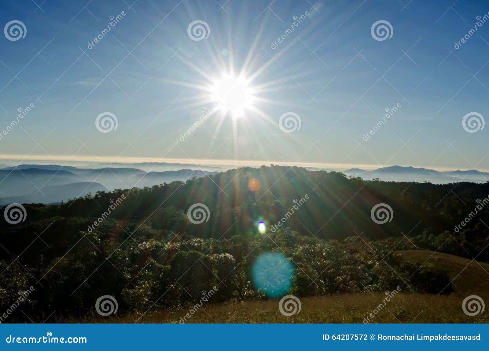 Salida del sol en el paisaje de las montañas