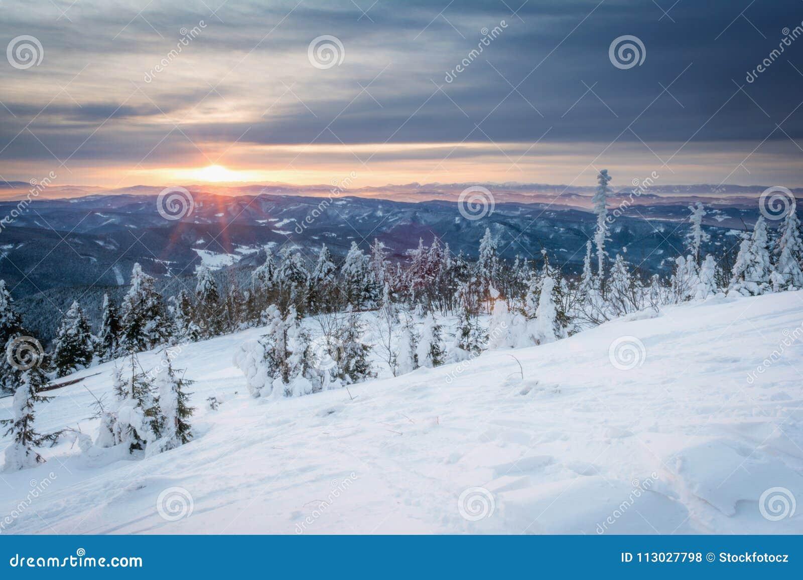 Salida del sol en montañas nevosas