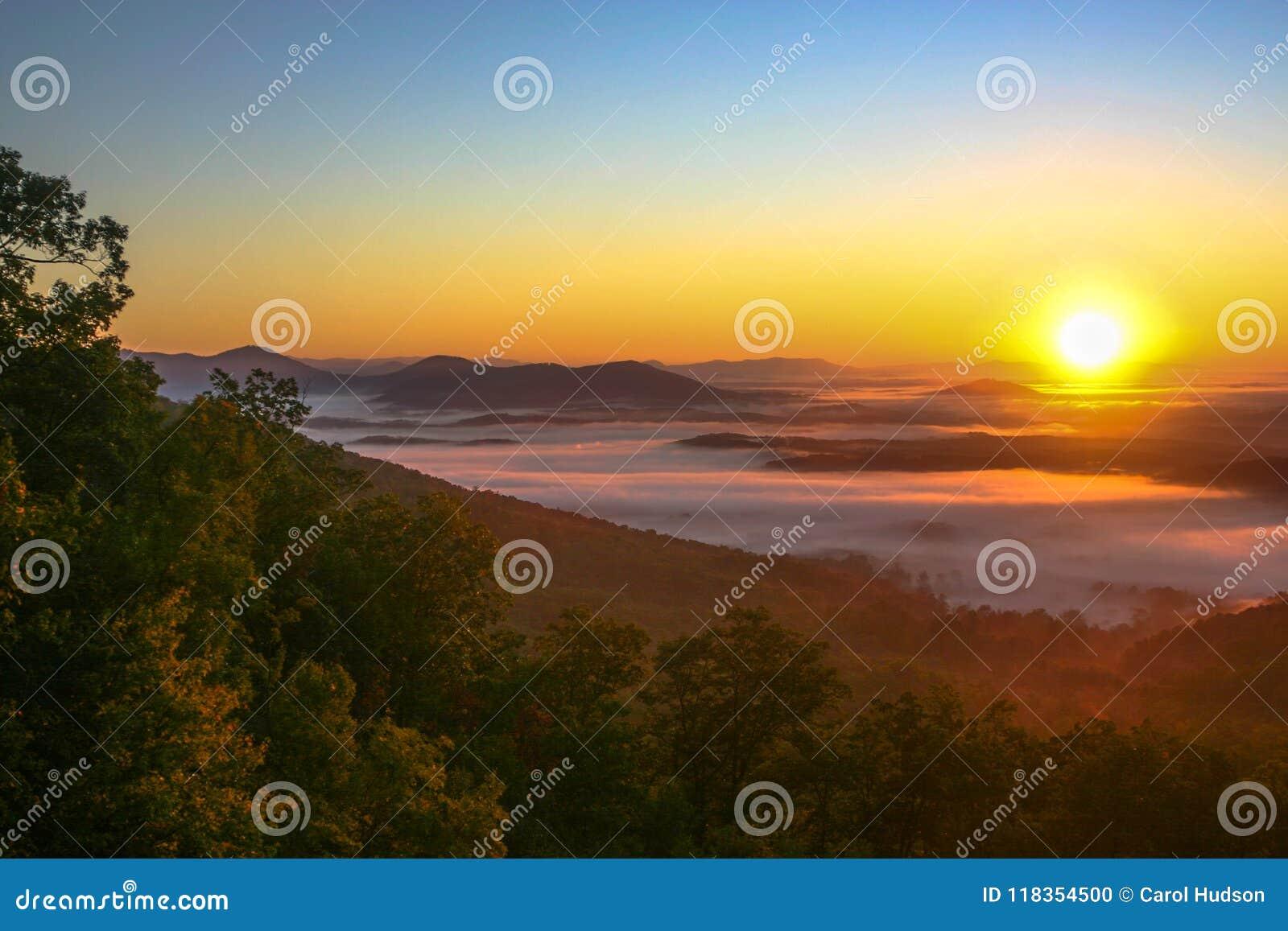 Salida del sol en señuelo del lago con niebla en el valle