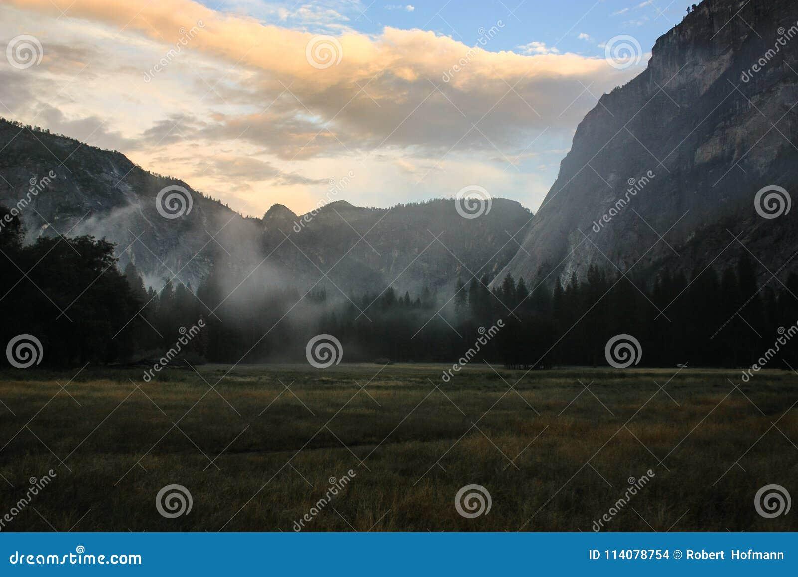 Salida del sol sobre el valle de Yosemite con la media bóveda un EL Capitan Mounta